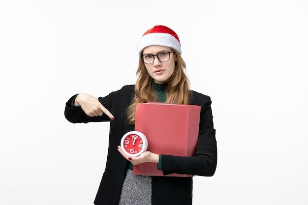 Vue de face jeune femme tenant horloge et fichiers sur mur blanc livre leçon college