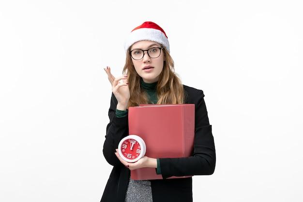 Vue de face jeune femme tenant horloge et fichiers sur mur blanc livres leçon college