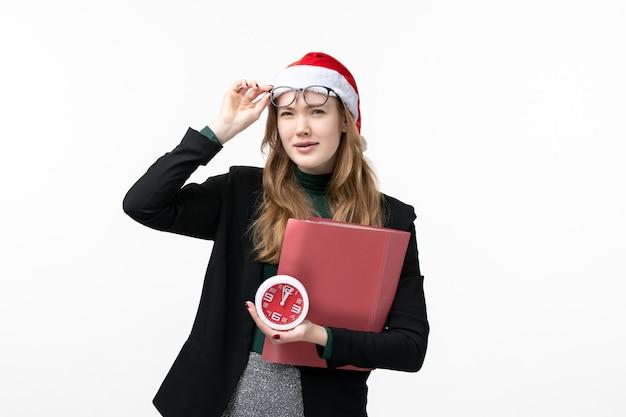 Vue de face jeune femme tenant l'horloge et les fichiers sur le sol blanc livre leçon collège