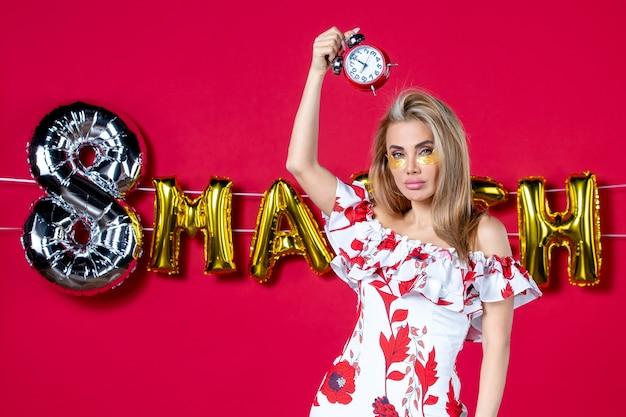 Vue de face jeune femme tenant des horloges en mars décorée de couleurs de féminité rouges maquillage féminin
