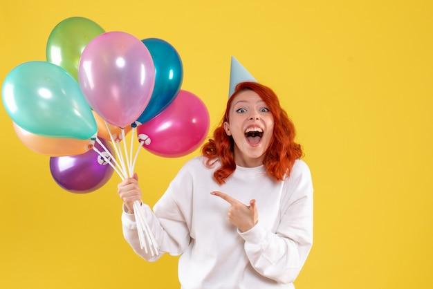 Vue de face de la jeune femme tenant de jolis ballons colorés sur mur jaune