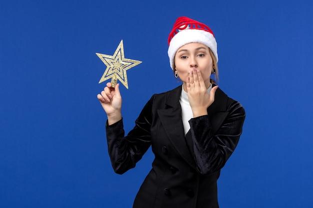 Vue de face jeune femme tenant un jouet en forme d'étoile sur le mur bleu femme de vacances de nouvel an