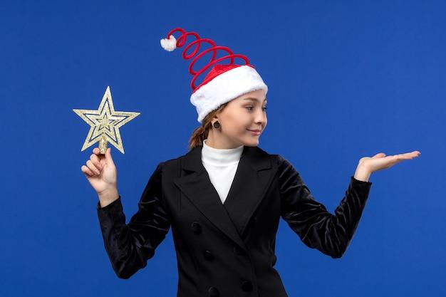 Vue de face jeune femme tenant un jouet en forme d'étoile sur mur bleu vacances femme nouvel an