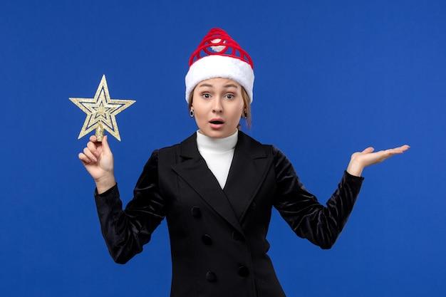 Vue de face jeune femme tenant un jouet en forme d'étoile sur le mur bleu vacances femme nouvel an
