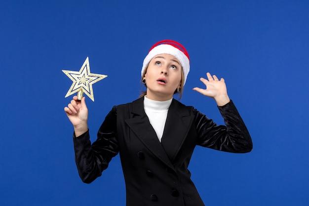 Vue de face jeune femme tenant un jouet en forme d'étoile sur mur bleu vacances nouvel an