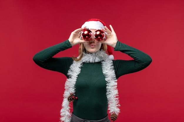Vue de face jeune femme tenant des jouets d'arbre de noël sur un bureau rouge