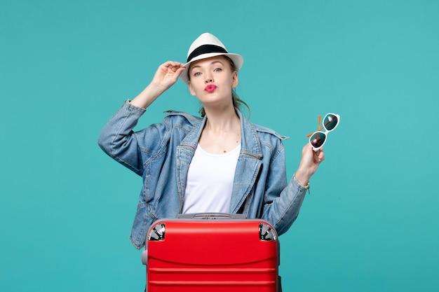 Vue de face jeune femme tenant des lunettes de soleil et portant un chapeau sur l'espace bleu