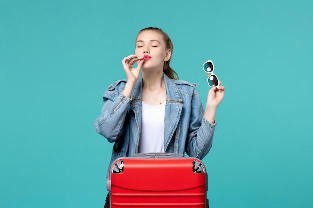 Vue de face jeune femme tenant des lunettes de soleil et se préparant pour des vacances sur l'espace bleu