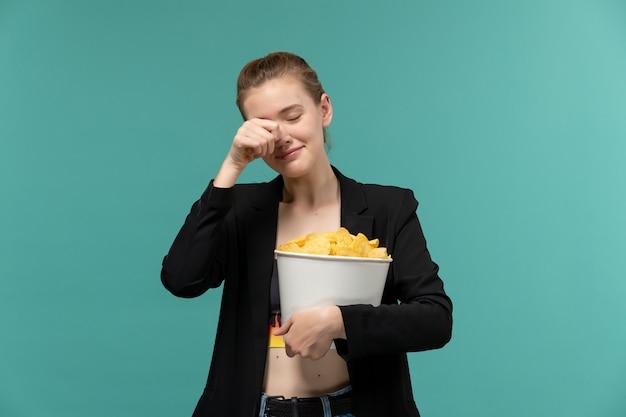 Vue de face jeune femme tenant et manger des chips regarder un film pleurer sur une surface bleue