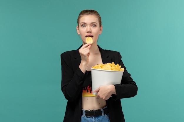 Vue de face jeune femme tenant et manger des chips regarder un film sur une surface bleu clair