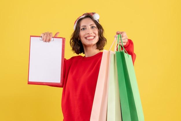 Vue de face jeune femme tenant note de fichier et paquets sur jaune