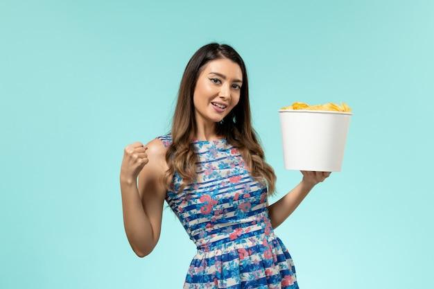 Vue de face jeune femme tenant le panier avec des croustilles sur un bureau bleu