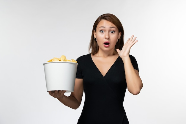 Vue de face jeune femme tenant le panier avec des croustilles et choqué sur une surface blanche