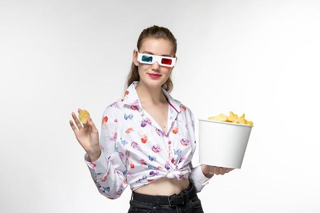 Vue de face jeune femme tenant le panier avec des croustilles en d lunettes de soleil souriant sur une surface blanche