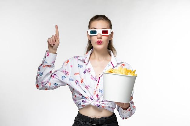Vue de face jeune femme tenant le panier avec des croustilles en d lunettes de soleil sur une surface blanche légère