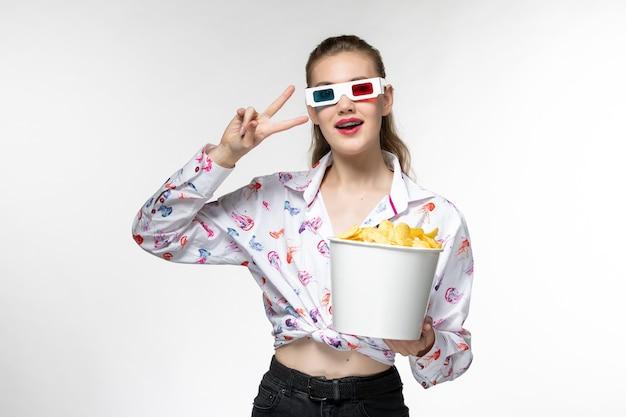 Vue de face jeune femme tenant le panier avec des croustilles en d lunettes de soleil sur une surface blanche