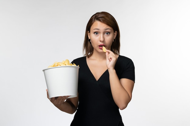 Vue de face jeune femme tenant le panier avec des croustilles et manger sur la surface blanche légère