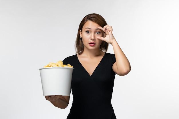 Vue de face jeune femme tenant le panier avec des croustilles et manger sur une surface blanche