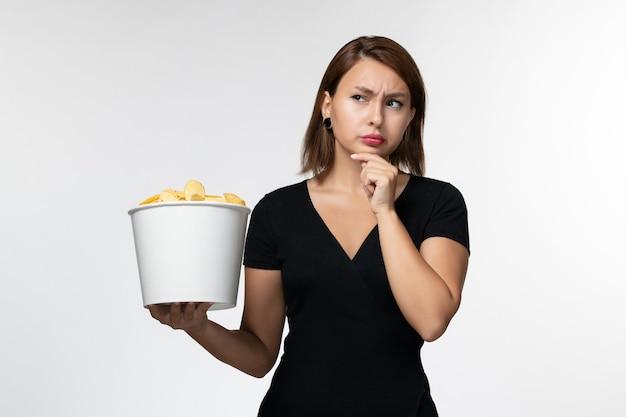 Vue de face jeune femme tenant le panier avec des croustilles pensant sur une surface blanche