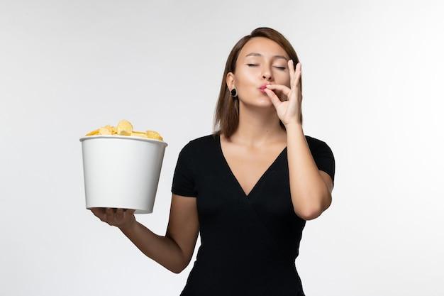 Vue de face jeune femme tenant le panier avec des croustilles et posant sur un bureau blanc clair