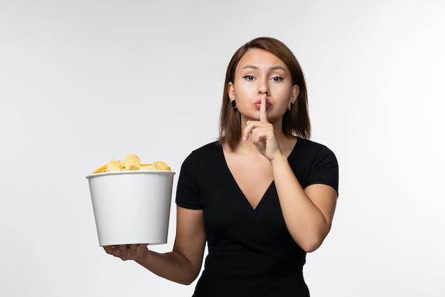 Vue de face jeune femme tenant le panier avec des croustilles et posant sur un bureau blanc