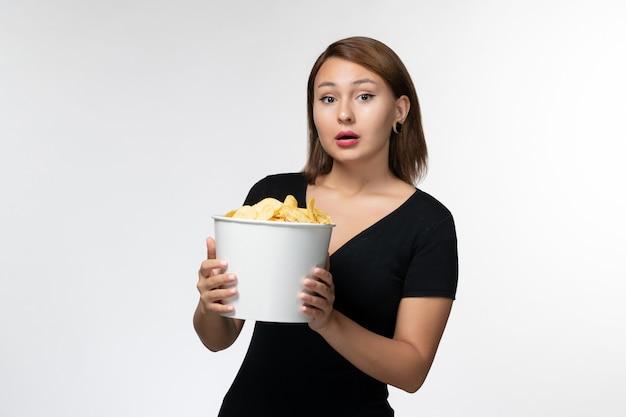 Vue de face jeune femme tenant le panier avec des croustilles et posant sur une surface blanche légère