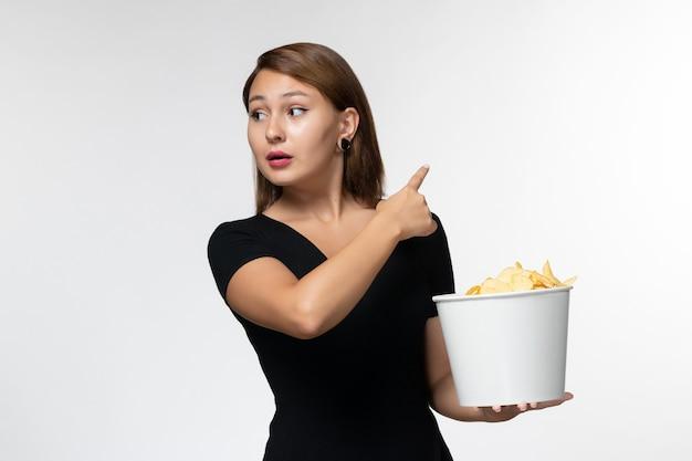 Vue de face jeune femme tenant le panier avec des croustilles regarder un film sur un bureau blanc
