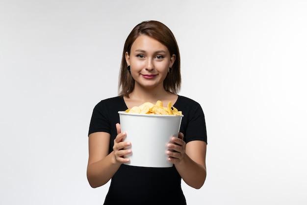 Vue de face jeune femme tenant le panier avec des croustilles et regarder un film en souriant sur une surface blanc clair
