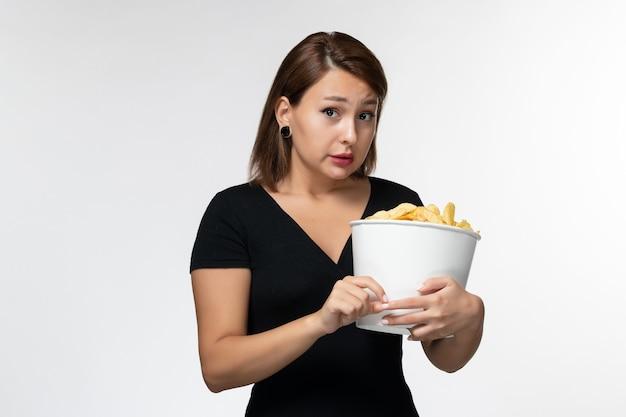 Vue de face jeune femme tenant le panier avec des croustilles regarder un film sur une surface blanche légère