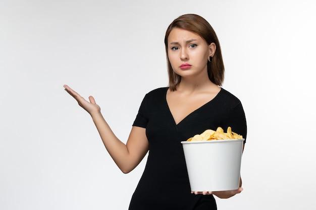Vue de face jeune femme tenant le panier avec des croustilles regarder un film sur une surface blanche
