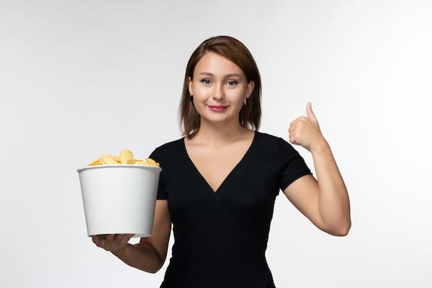 Vue de face jeune femme tenant le panier avec des croustilles souriant sur une surface blanche