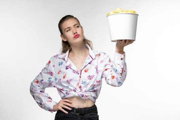 Vue de face jeune femme tenant le panier avec des croustilles sur une surface blanche