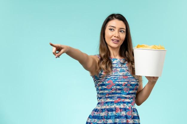 Vue de face jeune femme tenant le panier avec des croustilles sur une surface bleu clair
