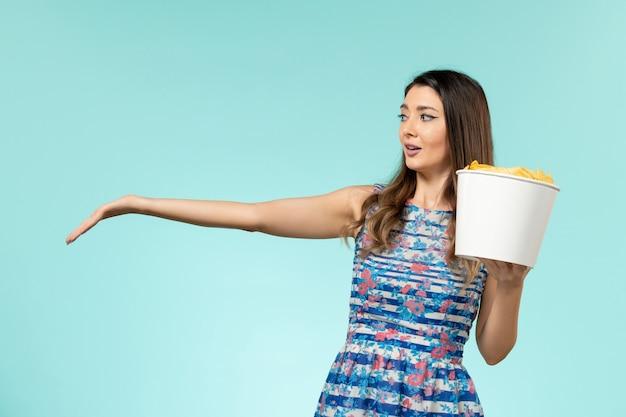 Vue de face jeune femme tenant le panier avec des croustilles sur la surface bleue