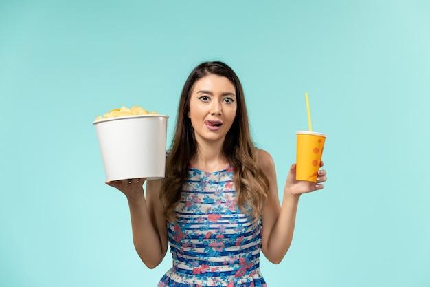 Vue de face jeune femme tenant le panier avec des frites et boire sur une surface bleu clair