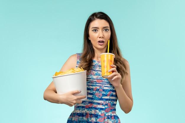 Vue de face jeune femme tenant panier avec frites et boisson sur la surface bleue