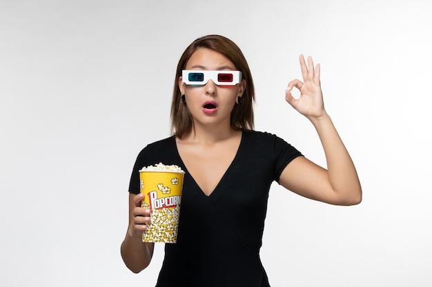 Vue de face jeune femme tenant un paquet de pop-corn dans des lunettes de soleil et regarder un film sur une surface blanche