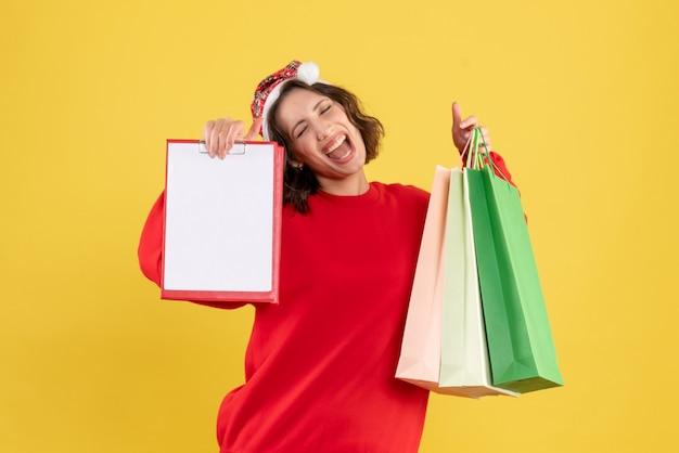 Vue de face jeune femme tenant des paquets et une note de dossier sur jaune