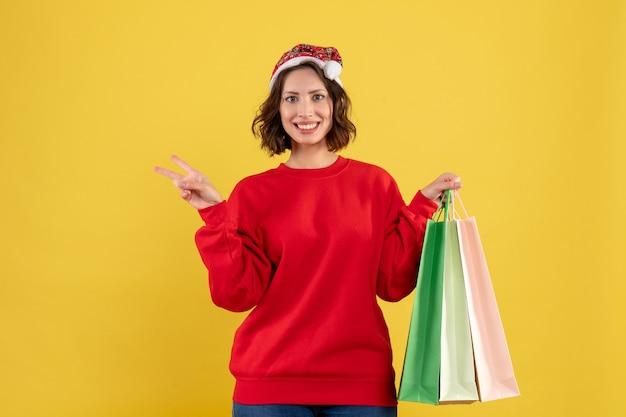 Vue de face jeune femme tenant des paquets de shopping sur jaune