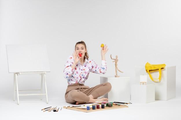 Vue de face jeune femme tenant des peintures colorées à l'intérieur de petites boîtes sur fond blanc