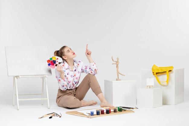 Vue de face jeune femme tenant des peintures pour dessiner sur fond blanc