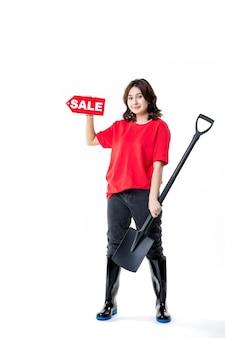 Vue de face jeune femme tenant une pelle noire et une vente rouge écrit sur fond blanc sol travail cimetière sol creuser travail émotion