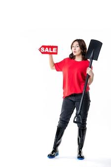 Vue de face jeune femme tenant une pelle noire et une vente rouge écrit sur fond blanc travail au sol cimetière travail émotion creuser
