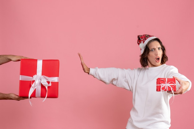 Vue de face de la jeune femme tenant peu de cadeau et n'acceptant pas de cadeau de l'homme sur le mur rose