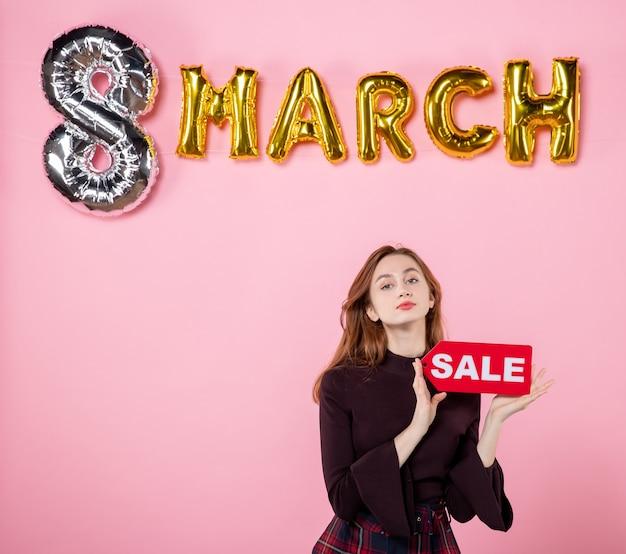 Vue de face jeune femme tenant une plaque signalétique de vente rouge sur la fête de mariage rose womens day présente des vacances de shopping