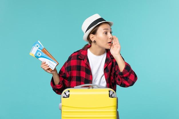 Vue de face jeune femme tenant le portefeuille avec des billets chuchotant sur l'espace bleu
