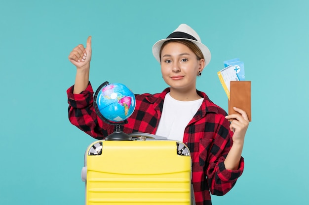 Vue de face jeune femme tenant le portefeuille avec des billets sur l'espace bleu clair