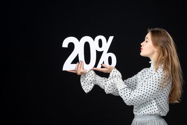Vue de face jeune femme tenant un pourcentage de remise d'écriture sur un mur noir