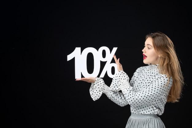 Vue de face jeune femme tenant le pourcentage de remise d'écriture