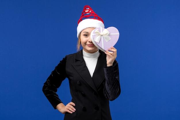 Vue de face jeune femme tenant présent en forme de coeur sur le mur bleu cadeau de vacances de nouvel an